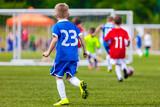 Soccer Kick; Running Soccer Football Players. Footballers Kicking Football Match; Young Soccer Players Running After the Ball. Footballers in Red and Blue Jersey Shirts Kicking Soccer Ball - 190699829