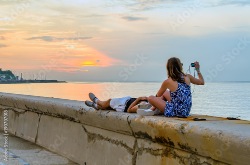 Aluminium Havana Young couple watching and photographing the sunset on the ocean