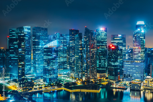 Singapore city skyline. Business district aerial view. Downtown landscape reflected in water at night in Marina Bay. Travel cityscape