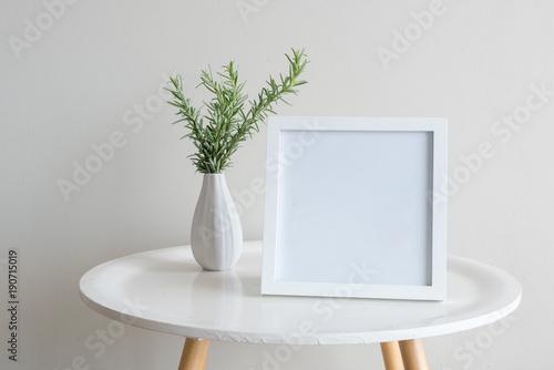 Zamyka up sprigs rozmaryn w małej białej wazie z puste miejsce kwadrata ramą na round stole przeciw beż ścianie