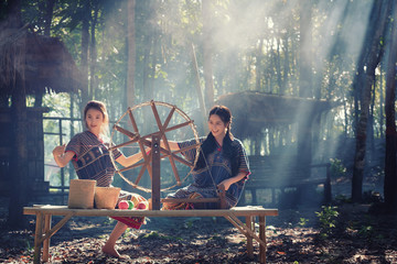 Two Beautiful Thai women smile in karen suit spinning thread on a bamboo mat in a forest nature local village Thailand
