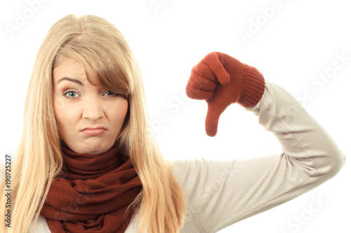 Unhappy woman in woolen gloves showing thumbs down, negative human emotions