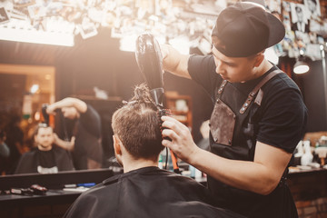 Barber shop. Barber dries hair of man with hair dryer and makes hair styling with hair dryer