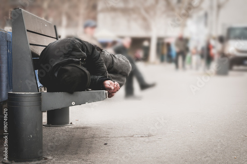 Leinwanddruck Bild Poor homeless man or refugee sleeping on the wooden bench on the urban street in the city, social documentary concept, selective focus