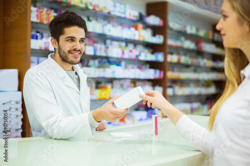 Staande foto Apotheek Experienced pharmacist counseling female customer in modern pharmacy