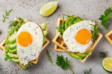 savory waffles with avocado, arugula and fried egg for breakfast