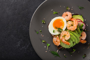 open sanwiches with dark rye bread, avocado, shrimps and soft boiled egg
