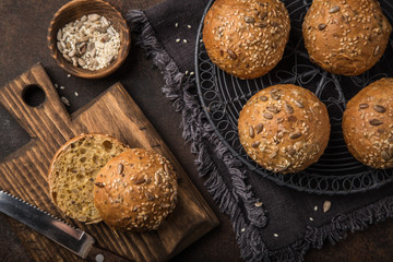 fresh baked buns with sesame, sunflower and flaxseed, wooden background