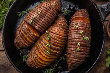 baked hasselback sweet potato on cast iron pan. wooden background,