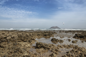 reef at low tide with tide pools and a kite surfer in the back