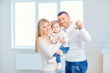 A happy family moves to a new apartment. Mother, father and child with boxes in the room of the new house. - 190761488
