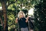 Cute little blonde girl playing on a tree swing outside - 190763450