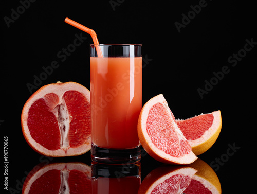 Aluminium Sap Glass of grapefruit juice and cut fruits on black background.