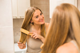Beautiful woman combing her hair  in the bathroom. - 190779448