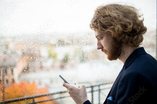 Young bearded man with smartphone messaging by window on rainy day