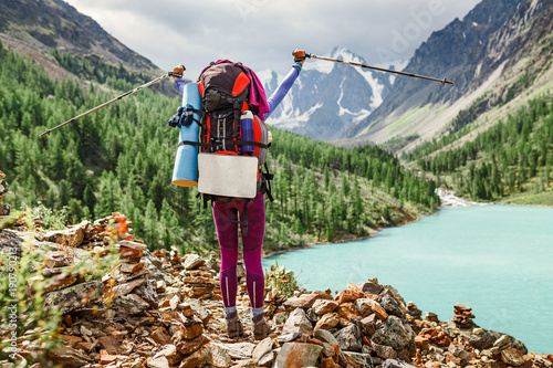 Aluminium Olijf girl hiker standing on a rock and looking at the lake in Altai mountains