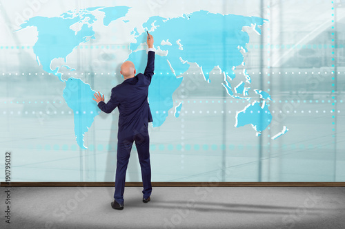 Foto Murales Businessman in front of a wall with a Connected world map on a uniform background - 3d render