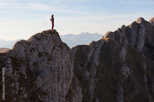 Woman high on cliff looking out at view of the deep canyon