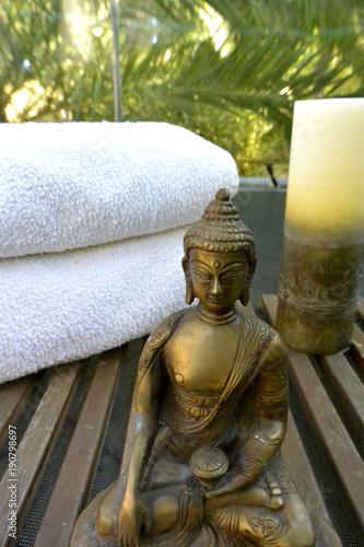 Fotobehang Boeddha Estatua de Buda con vela y toallas blancas para meditacion