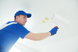 refurbishment. Painter painting ceiling with paint roller