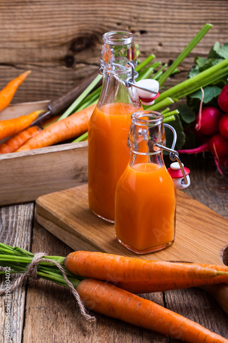 Keuken foto achterwand Sap Freshly squeezed carrot juice and organic raw vegetables
