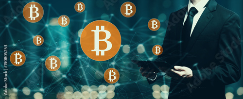 Bitcoin with businessman holding a tablet computer