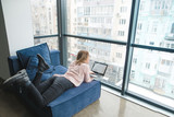A girl with a laptop lying on the couch near the panoramic window and working. Work in a modern office