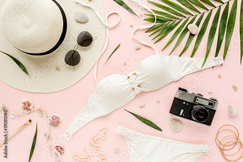 acaa2cb3 Feminine white swimsuit beach accessories, tropical palm leaf branches on  pink background. Travel vacation