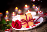 Romantic candle light dinner on Valentines Day with gift box, rose flower and and red wine
