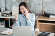 Young asian businesswoman talking phone and arms up with smiling face while working at her office desk, success in business concept
