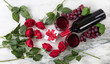 Romantic setting with red wine and roses on marble stone background