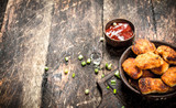 Chicken nuggets in a bowl with tomato sauce. - 190840435