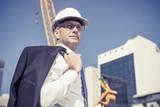 Senior elegant builder man in suit at construction site on sunny - 190840600