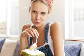 Cropped shot of adorable female wears t shirt and denim overalls, sips tasty exotic cocktail in cafteria, being alone, poses at camera. Teenage girl has summer vacations in tropical country.