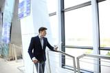 Businessman using digital tablet in airport departure lounge. - 190846245
