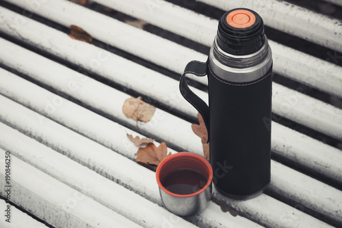 Thermos with cup stands on white bench