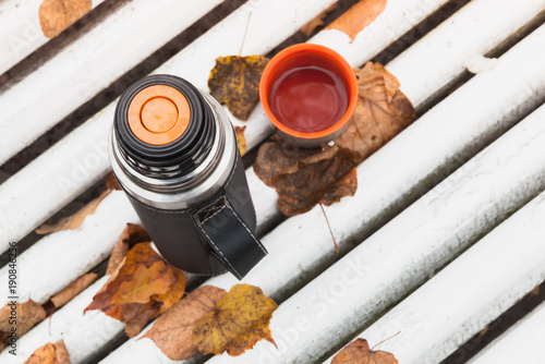 Thermos with cup of tea on white bench