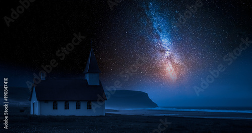 Fotobehang Nachtblauw Small church by sea in Iceland with stars at night