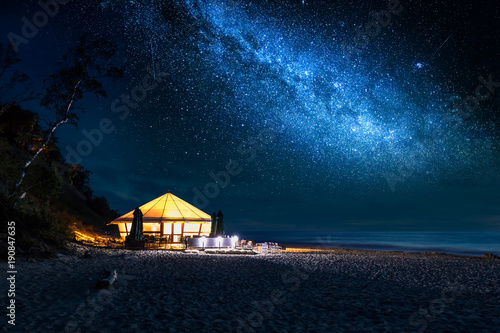 Fotobehang Strand Beach with glowing tent at night with stars