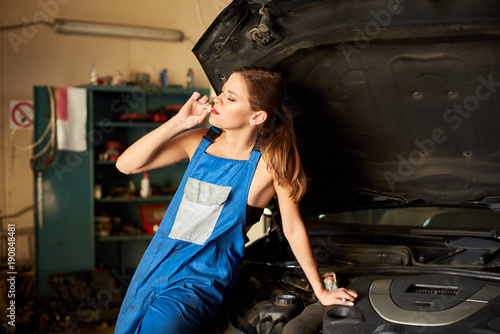 Young girl enjoys her cigarette sitting on a car in a garage.