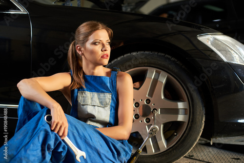Beautiful girl mechanic sits near the wheel of black car. Girl is dressed in work uniform and holds a wrench in her hands. In the wheel you can see the key for removing the wheel