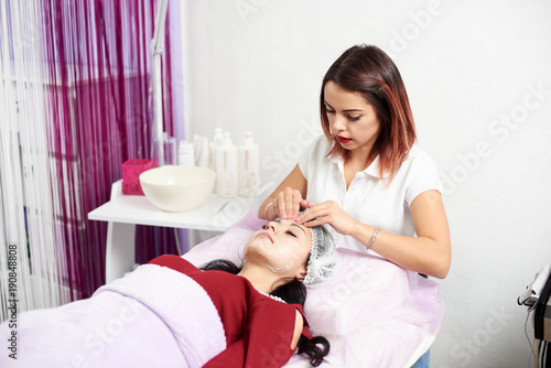 Cosmetologist applying cream to the face and massages woman. Cosmetology and professional skin care.