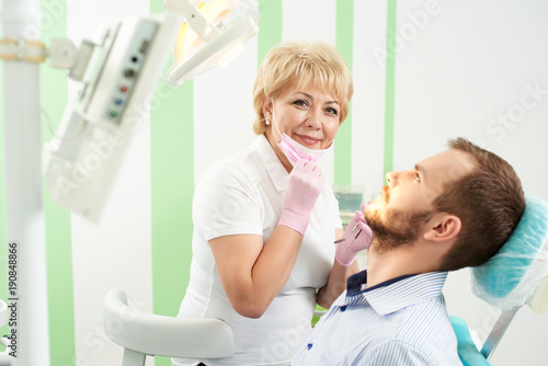 Pleasant woman dentist took off her mask and looks into the camera holding a tool, near her in the chair sits the patient