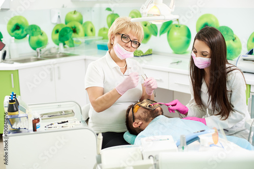 Attractive female dentist is smiling to the camera while holding medical instruments getting ready to attending the teeth of a male client of a dental office. Young brunette is assisting the doctor.