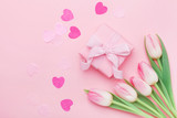 Spring flowers and present or gift box on pink pastel table top view. Greeting card for Womans or Mothers Day. Flat lay. - 190849619