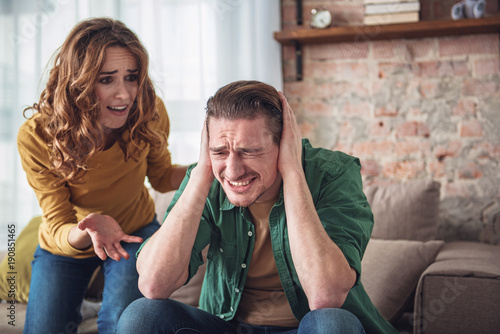 Listen to me. Angry man is closing his ears with desperation while his wife is shouting at him. Family conflict concept