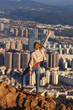 Girl standing on a rock on mountain top with city in the back - 190852018