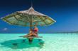 Young beautiful woman in purple bikinis under beach umbrella in the ocean