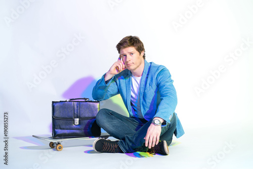 Fotobehang Skateboard Full length portrait of pensive young businessman sitting near skateboard. Modern bag locating on it. Profession and sport concept