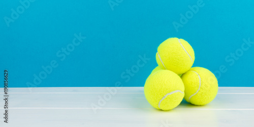 Fotobehang Tennis four tennis balls with blue background panorama
